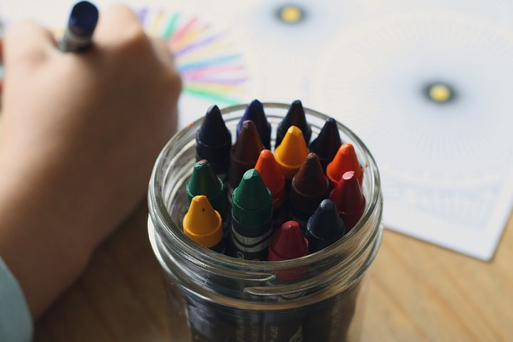 Image of crayons in the foreground with a child drawing in the background.